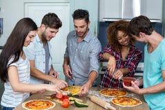 Amis préparant la pizza sur la table de cuisine Image stock