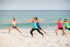 Amis pratiquant la pose du guerrier 2 sur le rivage à la plage Photo libre de droits