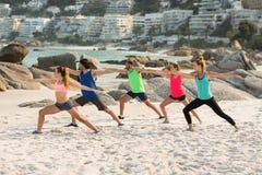 Amis pratiquant la position de guerrier sur le rivage à la plage Image libre de droits