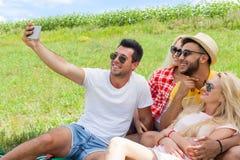 Amis prenant à photo de selfie la campagne futée de pique-nique de téléphone les jeunes Images stock