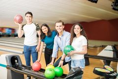 Amis prenant des boules tout en traînant au bowling Photos libres de droits