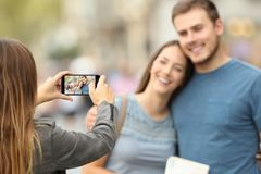 Amis prenant des photos avec un téléphone intelligent sur la rue Photographie stock libre de droits