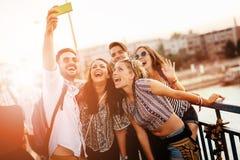 Amis prenant des selfies et le sourire Photos libres de droits