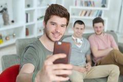 Amis prenant des selfies sur le smartphone dans la maison avec du charme Photos libres de droits