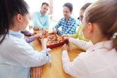 Amis prenant des tranches de pizza Images stock