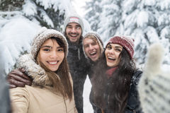 Amis prenant la neige Forest Young People Group Outdoor de sourire de photo de Selfie Images libres de droits