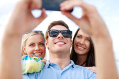 Amis prenant la photo avec l'appareil-photo de smartphone Photographie stock