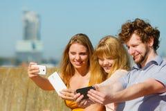 Amis prenant la photo de selfie avec le smartphone Images stock