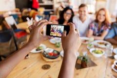 Amis prenant la photo par le smartphone au restaurant Photographie stock