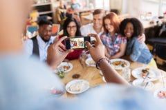 Amis prenant la photo par le smartphone au restaurant Photo stock