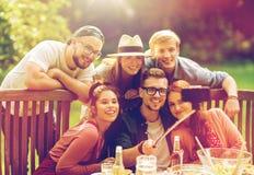 Amis prenant le selfie à la partie dans le jardin d'été Photographie stock