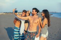 Amis prenant le selfie à la plage le jour ensoleillé Photographie stock