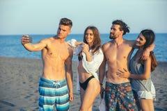 Amis prenant le selfie à la plage le jour ensoleillé Photos libres de droits