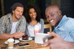 Amis prenant le selfie à la table en bois dans le café Photos libres de droits