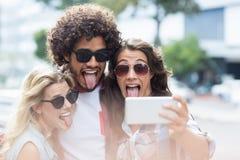Amis prenant le selfie à un téléphone portable Image stock