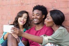 Amis prenant le selfie à un téléphone portable Photographie stock libre de droits