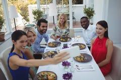Amis prenant le selfie au téléphone portable tout en ayant le repas Image stock