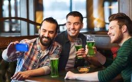 Amis prenant le selfie avec de la bière verte au bar Photo libre de droits