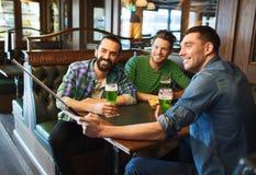 Amis prenant le selfie avec de la bière verte au bar Images stock