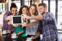 Amis prenant le selfie avec le comprimé numérique dans le restaurant Photographie stock libre de droits