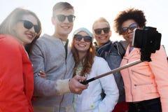 Amis prenant le selfie avec le smartphone sur le bâton Photo stock