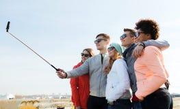 Amis prenant le selfie avec le smartphone sur le bâton Photos stock