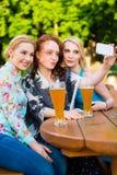 Amis prenant le selfie avec le smartphone dans le jardin de bière Photographie stock