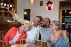 Amis prenant le selfie avec le téléphone portable dans la barre Images stock