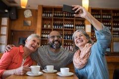Amis prenant le selfie avec le téléphone portable dans la barre Image libre de droits