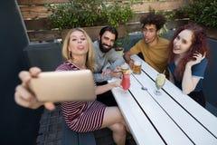 Amis prenant le selfie avec le téléphone portable tout en ayant des boissons dans la barre Photos libres de droits