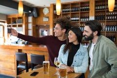 Amis prenant le selfie avec le téléphone portable tout en ayant le verre de bière Image libre de droits
