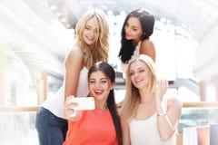Amis prenant le selfie dans le centre commercial Images stock