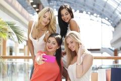 Amis prenant le selfie dans le centre commercial Photo stock
