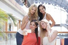 Amis prenant le selfie dans le centre commercial Photos stock