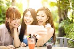 Amis prenant le selfie dans le restaurant de jardin Photo stock