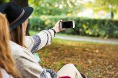 Amis prenant le selfie en parc Images stock
