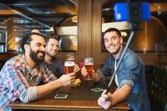 Amis prenant le selfie et buvant de la bière à la barre Photo stock