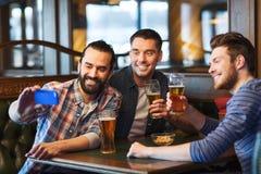 Amis prenant le selfie et buvant de la bière à la barre Images stock