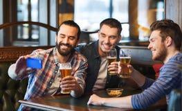 Amis prenant le selfie et buvant de la bière à la barre Photos stock