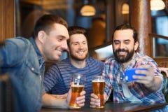 Amis prenant le selfie et buvant de la bière à la barre Photos libres de droits