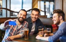 Amis prenant le selfie et buvant de la bière à la barre Images libres de droits