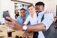 Amis prenant le selfie et buvant de la bière à la barre Image libre de droits