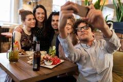 Amis prenant le selfie par le smartphone à la barre ou au café Photo libre de droits
