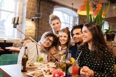 Amis prenant le selfie par le smartphone à la barre ou au café Images stock