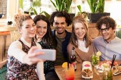 Amis prenant le selfie par le smartphone à la barre ou au café Photos libres de droits