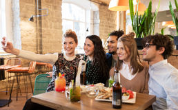 Amis prenant le selfie par le smartphone à la barre ou au café Images libres de droits