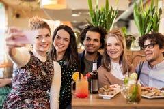 Amis prenant le selfie par le smartphone à la barre ou au café Image stock