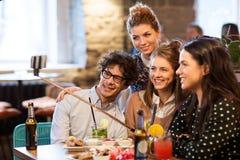 Amis prenant le selfie par le smartphone à la barre ou au café Photographie stock libre de droits