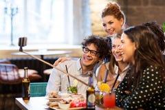 Amis prenant le selfie par le smartphone à la barre ou au café Image libre de droits
