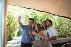 Amis prenant le selfie tout en ayant l'alcool au compteur Image stock